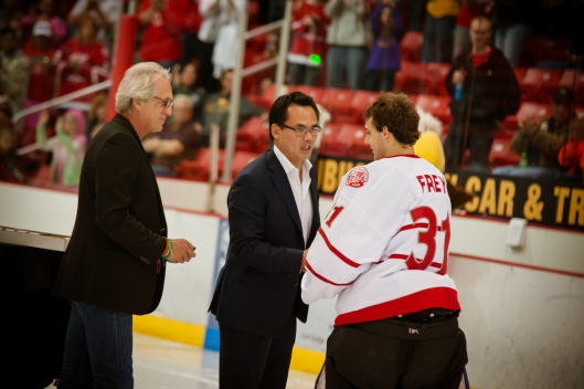 Brad Kwong, center, congratulates on of his team's players (Photo/Dubuque Fighting Saints).