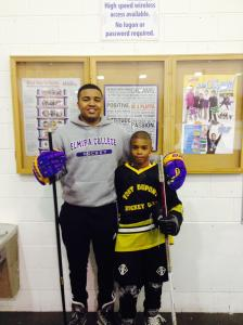 Elmira College hockey player and Fort Dupont alum Donnie Shaw III, left, helps out  at his old rink.
